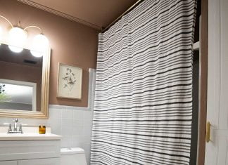 Beautiful black and white shower curtain hanging from a rod installed on the ceiling