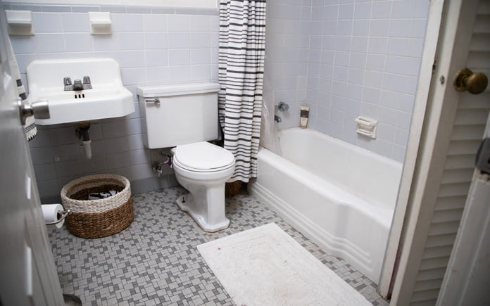 Unattractive mid-century bathroom with institutional tile floors and a basket under the sink