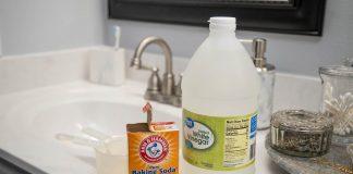 Box of baking soda and bottle of white vinegar, seen beside a bathroom sink