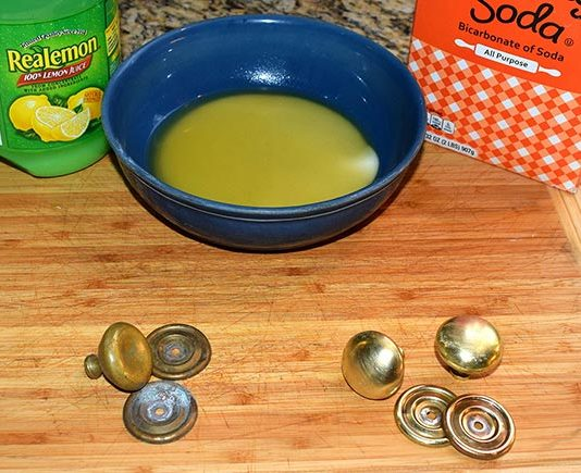 Display of lemon juice, baking soda and a bowl filled with these mixed ingredients. Old, tarnished knobs are on the left. Clean brass knobs are on the right.