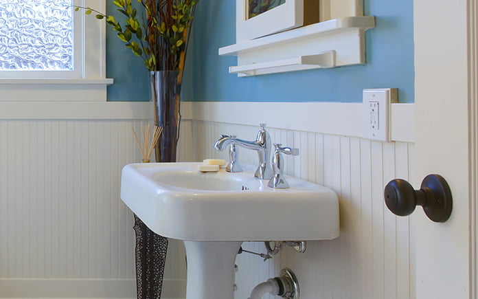 Cast iron sink in an updated bathroom with wainscoting