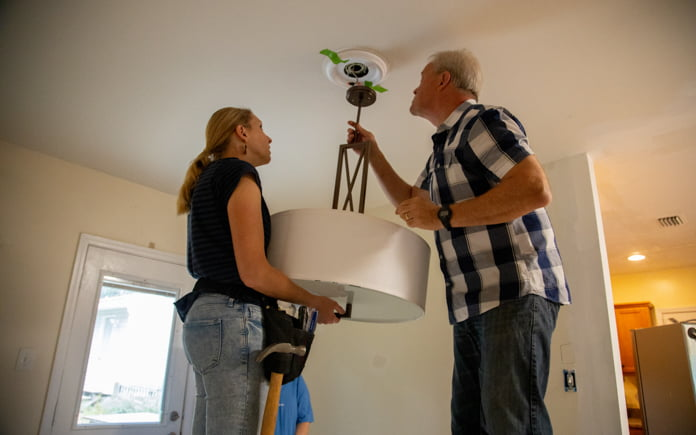 Today's Homeowner hosts Chelsea Lipford Wolf and Danny Lipford install ceiling medallion in Dawn Nelson's dining room
