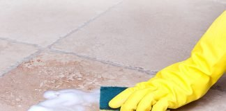 Gloved hand scrubbing ceramic tile floor with ammonia and liquid dish soap