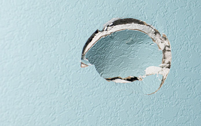 Hole in turquoise-painted drywall, from a doorknob