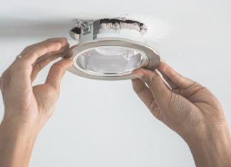 Closeup of hands installing a motion sensor ceiling light