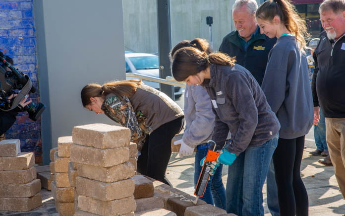 Marianna Middle School students apply landscape adhesive to Pavestone blocks in Florida