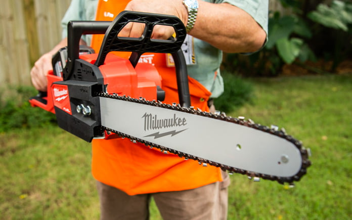 Dan, a Home Depot employee, stands outdoors holding Milwaukee's M18 FUEL 16-inch 18-Volt Brushless Cordless Chainsaw.