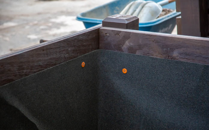 Roofing underlayment, as seen applied inside the walls of a planter built from pressure-treated wood