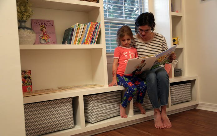 A mother and daughter read a book while sitting on a DIY window seat bookcase built around an arched window. The bookcase is filled with toys and books.