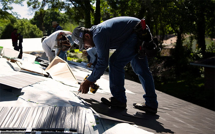 Workers install new metal roofing over asphalt shingles