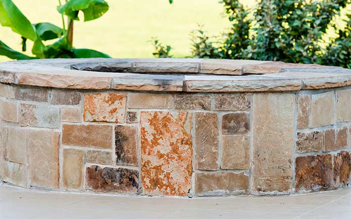 Brick fire pit installed over concrete patio with gray mortar between bricks