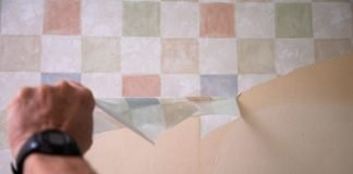 Removing checkered wallpaper from a wall.
