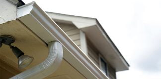 Close view of gutters and downspouts on a home with wood siding