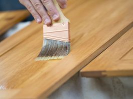 Paintbrush staining a wooden cabinet