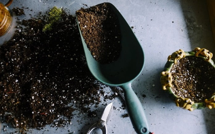 Soil on a table next to a shovel and a pot