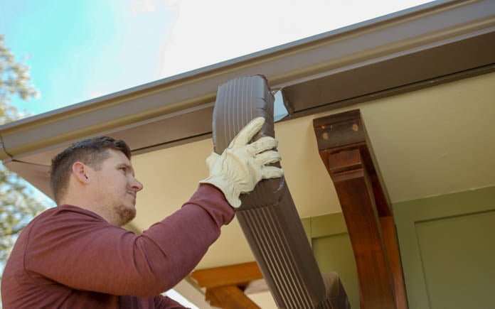 Marc Ingram removes a downspout from a gutter