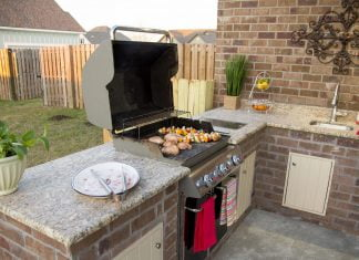 An outdoor kitchen area in a backyard, featuring a granite countertops, a grill and a sink