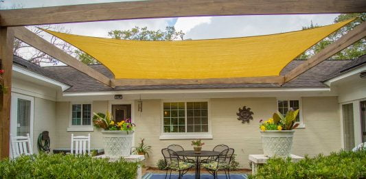 Shade sail over a brick patio, seen from ground level