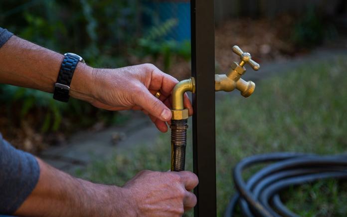 Man adjusts garden host dispenser
