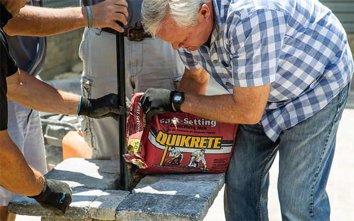 """""""Today's Homeowner"""" host Danny Lipford pours Quikrete Fast-Setting Concrete Mix into a post hole."""