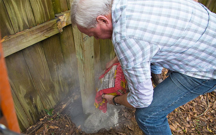 """""""Today's Homeowner"""" host Danny Lipford pours concrete mix into a fence post hole"""
