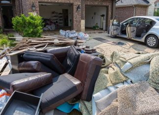 Flooded house, seen outside, after the storm, with furniture and water-damaged items removed from the home