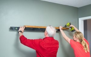 """Today's Homeowner"" hosts Danny Lipford and Chelsea Lipford Wolf install a picture ledge"