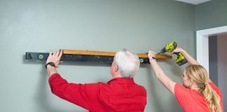 Danny Lipford and Chelsea Lipford Wolf install a picture ledge to a wall in Judy Laurence's family room