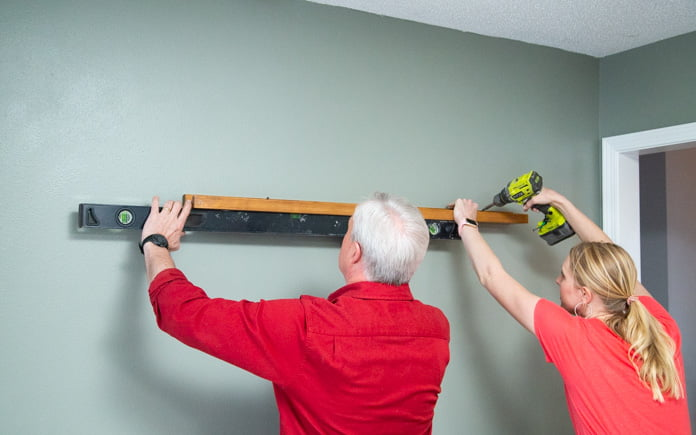 Danny Lipford and Chelsea Lipford Wolf install picture ledges to the wall in Judy Laurence's family room