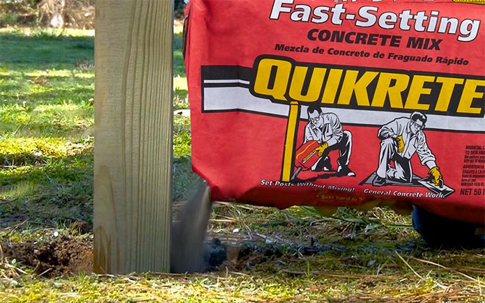 Closeup of Quikrete Fast-Setting Concrete Mix poured into a post hole