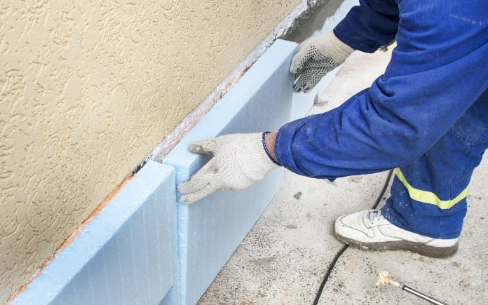 A person wearing a blue workmen suit, white gloves, and white sneakers repairs the foundation of a home.