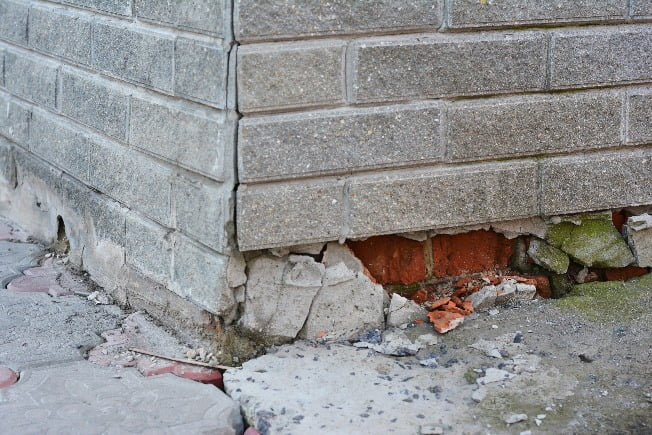A grey brick foundation of a home is crumbling and needs repair.