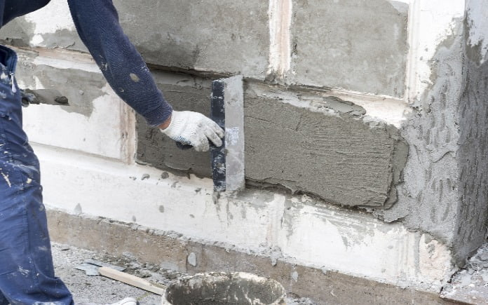 A person wearing white workmen gloves repairs the foundation of a home.
