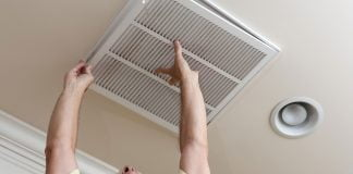 Man with short sleeve shirt replacing AC filter in the ceiling