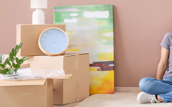 Stacked items, ready for moving, including a gold clock, artwork and several filled moving boxes