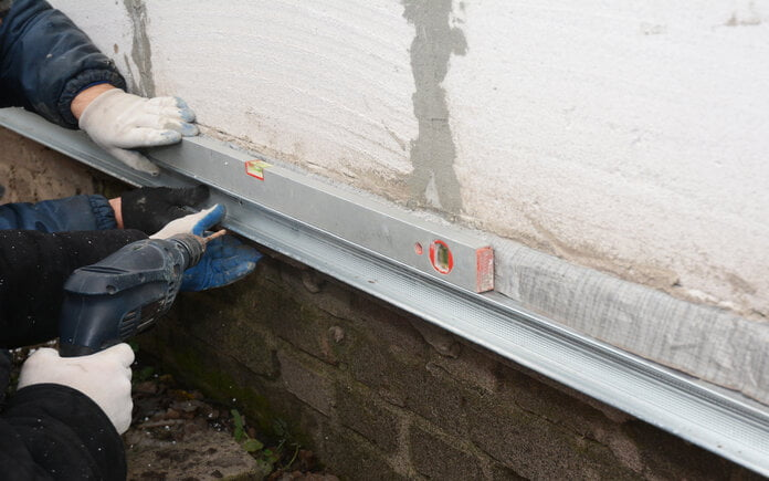 Two people wearing workmen gloves repair the foundation of a home using metal beams.