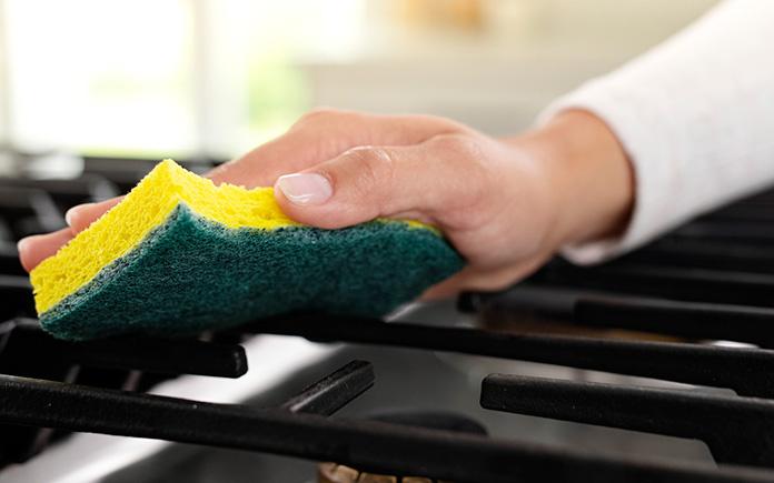 Woman cleans a gas grill with her Scotch-Brite Heavy Duty Scrub Sponge