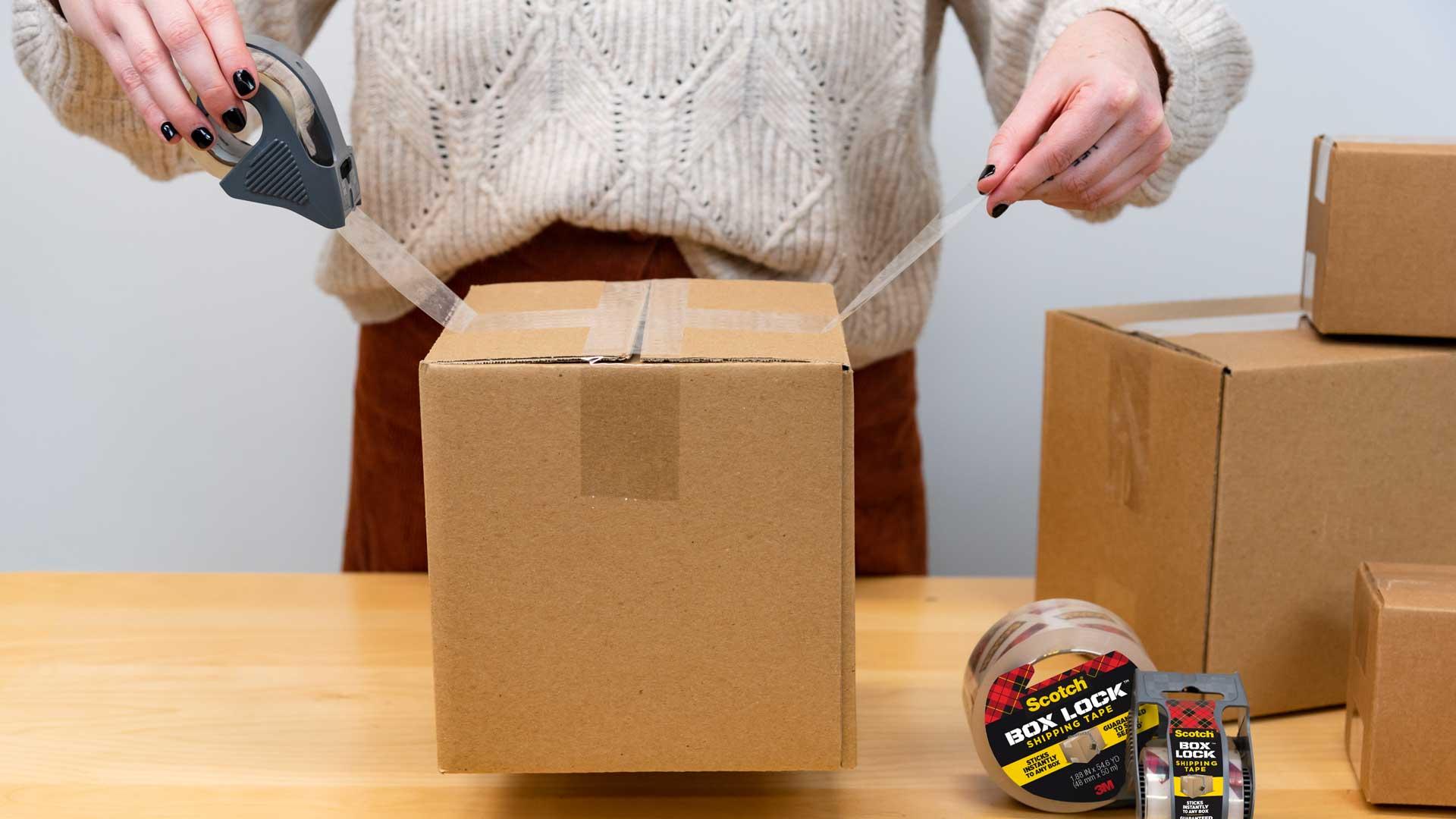 Woman wraps cardboard moving box with Scotch Box Lock shipping tape.