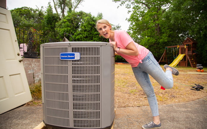 """""""Today's Homeowner"""" co-host Chelsea Lipford Wolf leaning against her new American Standard HVAC unit"""