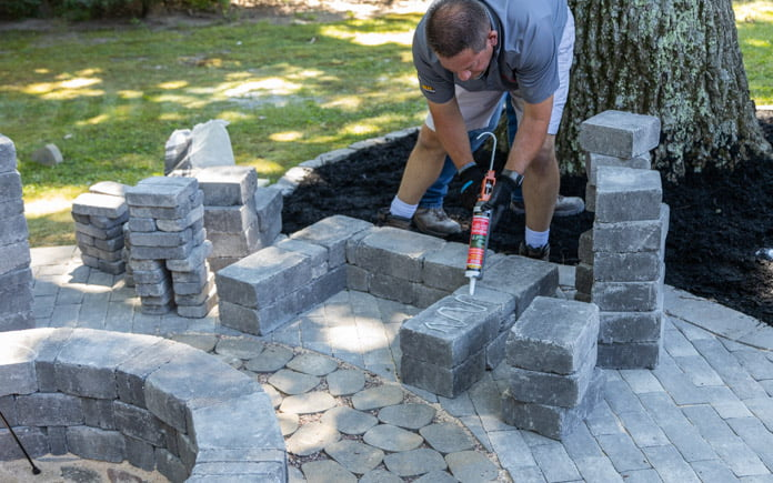 Man wearing a Quikrete shirt applies sealant to the base of a chair made of Pavestone pavers