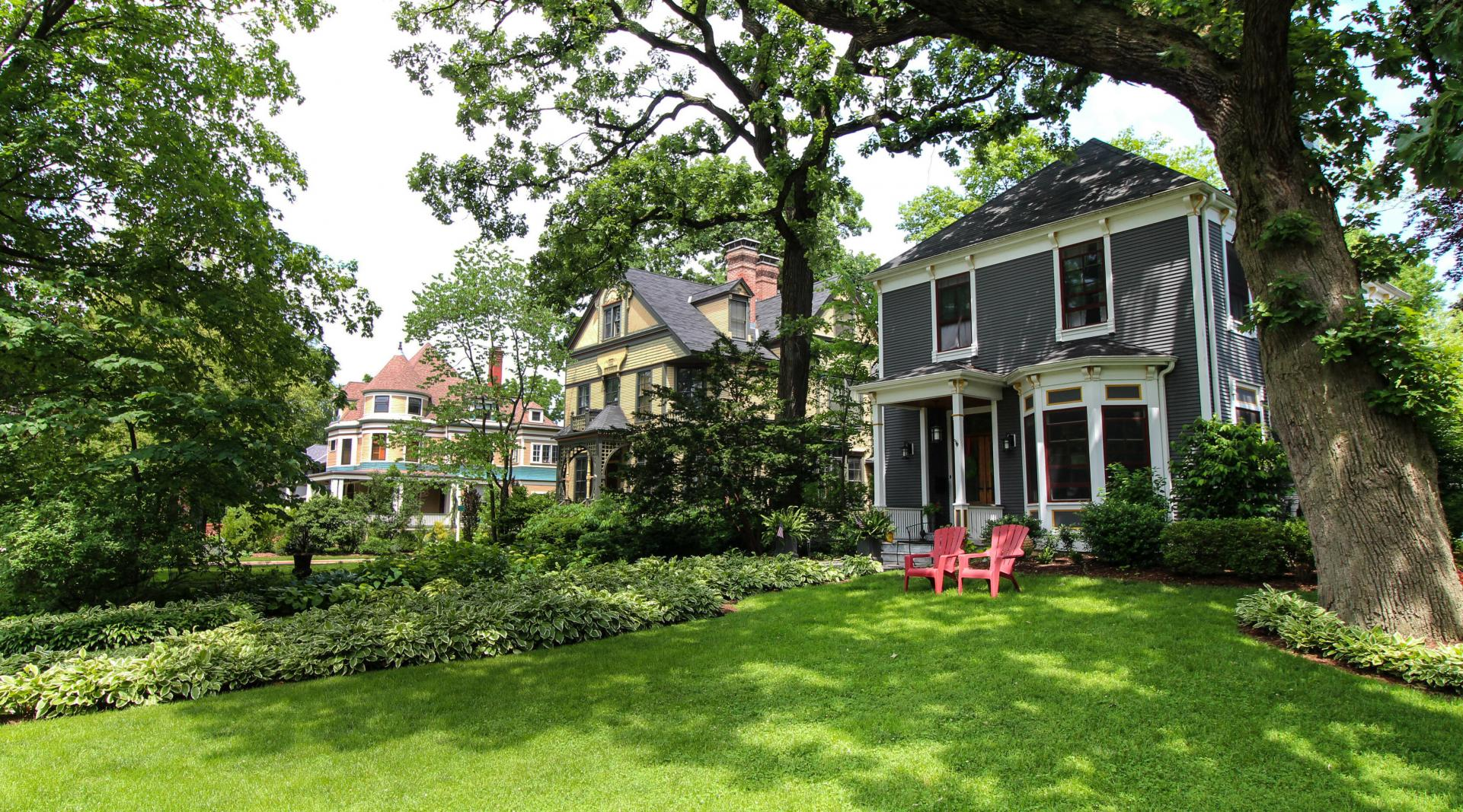 A Chicago home with large green front yard and red lawn chairs.