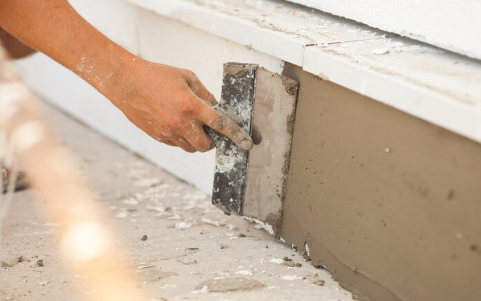 A person repairs the foundation of a home using plaster.