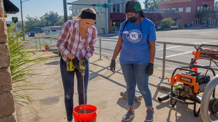 """""""Today's Homeowner"""" co-host Chelsea Lipford Wolf mixes concrete in a bucket"""