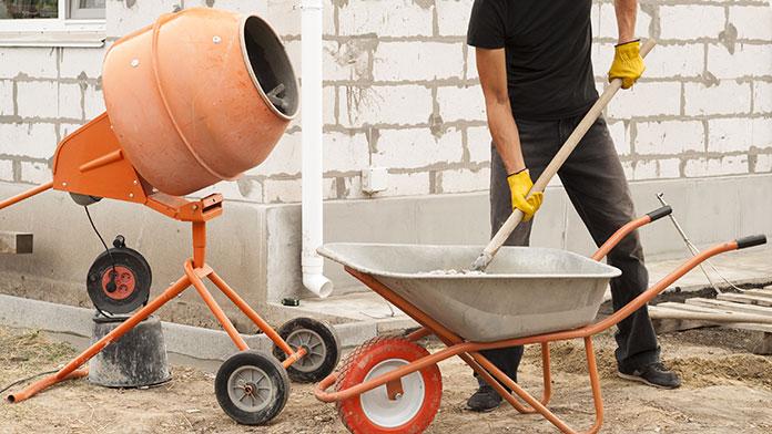 Man loads portable concrete mixer from concrete in a wheelbarrow